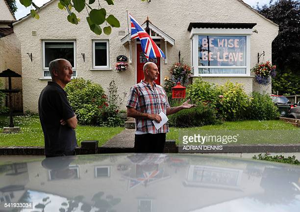 ProBrexit supporter Trevor Hatcher discusses the upcoming referendum vote with a neighbour outside his house in Carshalton south of London on June 21...