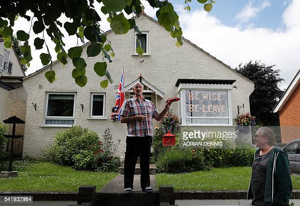 ProBrexit supporter Trevor Hatcher is given a packet of biscuits from a neighbour as they discuss the upcoming referendum vote outside his house in...