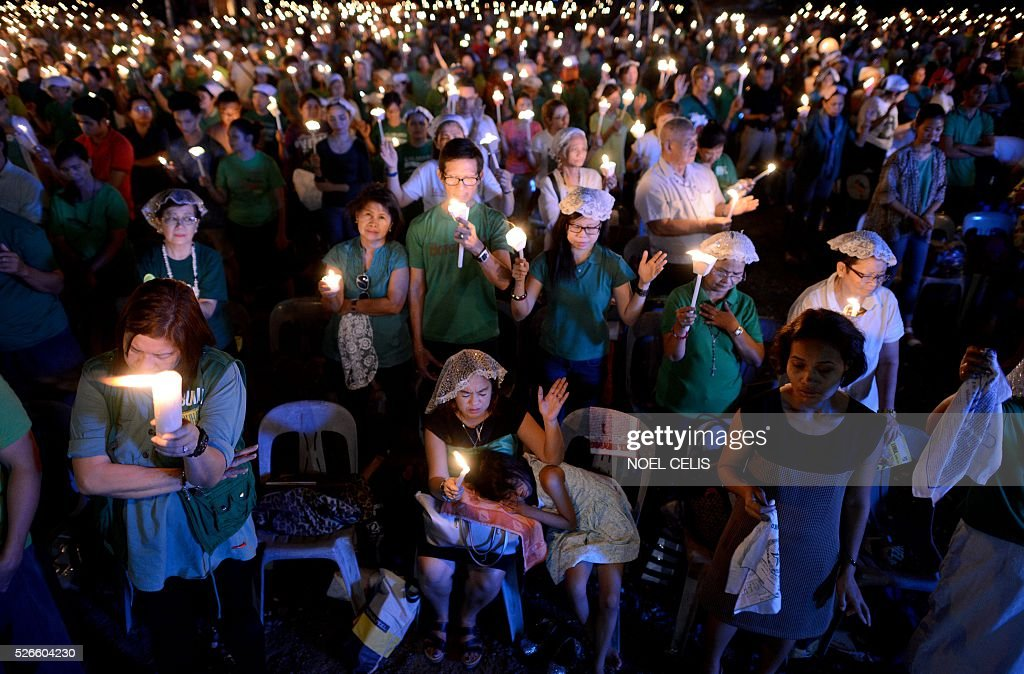Pro-Catholic Born again religious group El Shaddai hold candles during a prayer vigil overnight celebration in Manila on May 1, 2016. More than 17,000 positions ranging from president to town councillors will be contested when the Philippines holds national elections on May 9, 2016. About 80 percent of the Philippines' 100 million people are Catholic, a legacy of Spanish colonial rule that ended in the late 1800s. / AFP / NOEL
