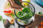 Man cooking healthy detox smoothie with fresh fruits and green spinach. Lifestyle detox concept