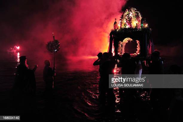 A procession headed by a priest walks into the sea at a beach at Tinos island during the celebrations of the Good Friday ahead of the Orthodox Easter...