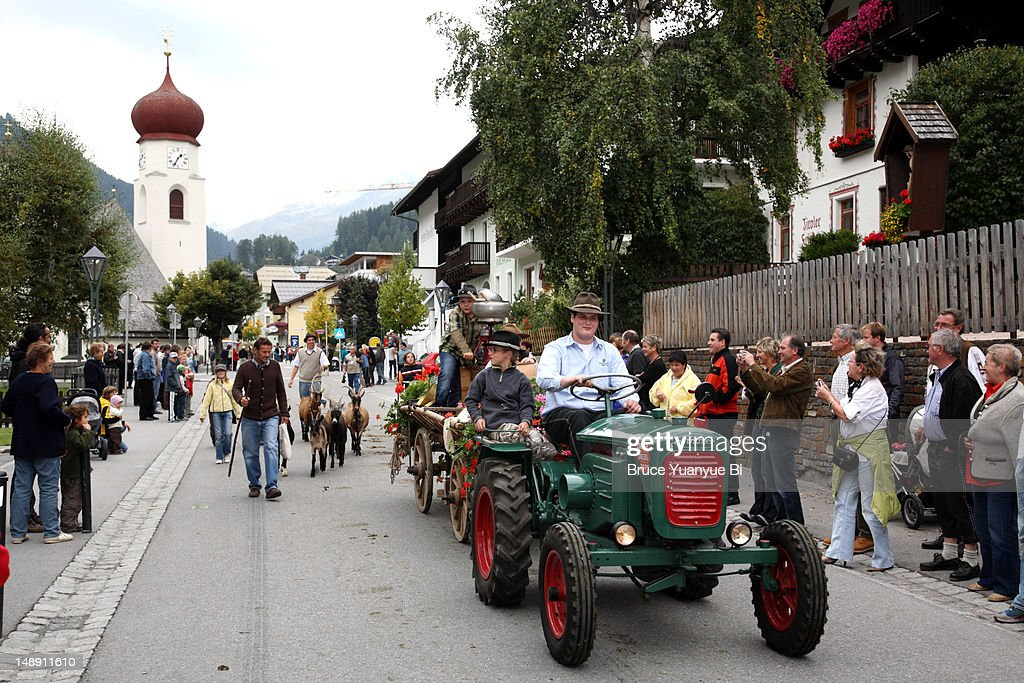 Procession of Alpine cattle drive festival through pedestrian zone in town.