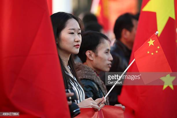 A proChina activist holds a Chinese flag as he demonstrates near Parliament ahead of a visit by China's President Xi Jinping on October 20 2015 in...
