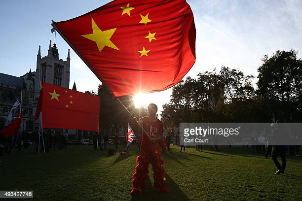 A proChina activist waves a Chinese flag as he demonstrates near Parliament ahead of a visit by China's President Xi Jinping on October 20 2015 in...