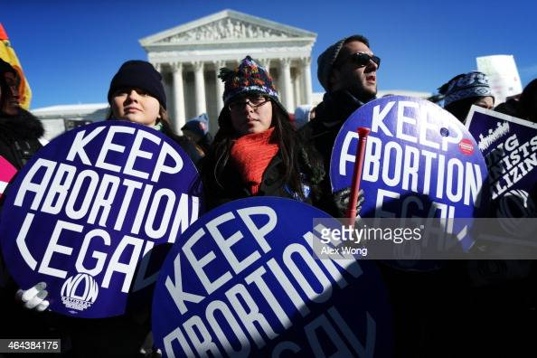 Prochoice activists hold signs as marchers of the annual March for Life arrive in front of the US Supreme Court January 22 2014 on Capitol Hill in...