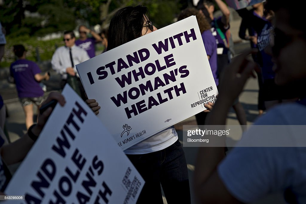 Pro-choice advocates hold signs outside the U.S. Supreme Court before rulings in Washington, D.C., U.S., on Monday, June 27, 2016. A divided U.S. Supreme Court struck down a Texas law that had threatened to close three-quarters of the states abortion clinics by putting new requirements on facilities and doctors. Photographer: Andrew Harrer/Bloomberg via Getty Images