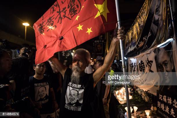 A prodemocracy activist carries an upturned Chinese national flag as he visits a makeshift memorial for the late Chinese Nobel laureate Liu Xiaobo...