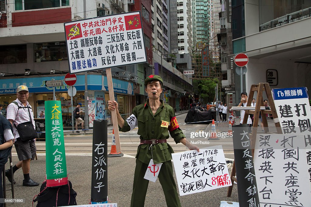 Pro-Democracy activist dressed like a Chinese Red Guard shows a placard with slogan against the government in Hong Kong, July 1 2016. Pro Democracy protesters march as the city marks the 19th anniversary of the handover from Uk to China.