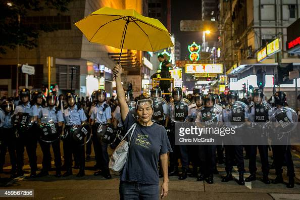 A prodemocracy activist holds a yellow umbrella in front of a police line on a street in Mongkok district on November 25 2014 in Hong Kong The Mong...
