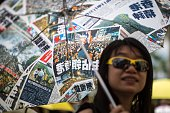 A prodemocracy activist shelters from the sun under an umbrella designed with images from the Occupy Central protests which took place late last year...