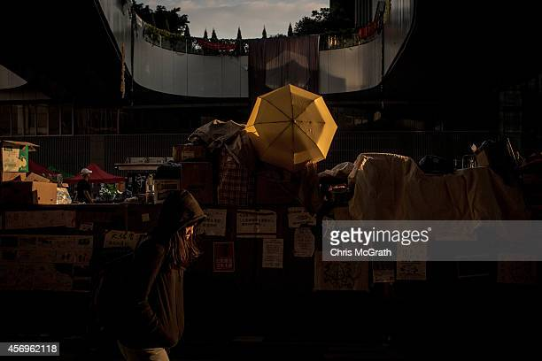 A prodemocracy activist walks in the street in the early hours of the morning outside Hong Kong's Government complex on October 10 2014 in Hong Kong...