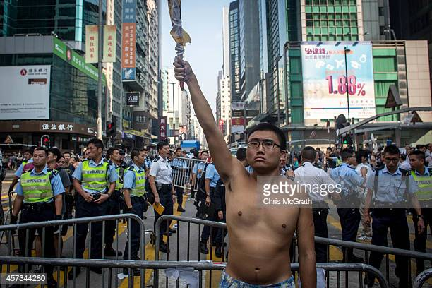 A prodemocracy activist waves a banner in front of a police barricade after they managed to reclaim one block after the police launched a dawn raid...