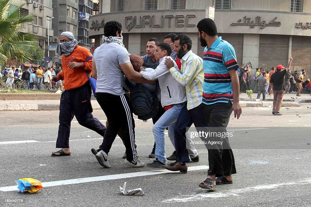Prodemocracy activists carry a wounded Egyptian who wounded during the intervention of Egyptian security forces during protests marking the...