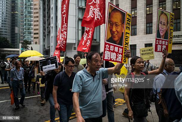 Prodemocracy activists carry pictures of the visiting Chairman of the Standing Committee of China's National People's Congress Zhang Dejiang along...