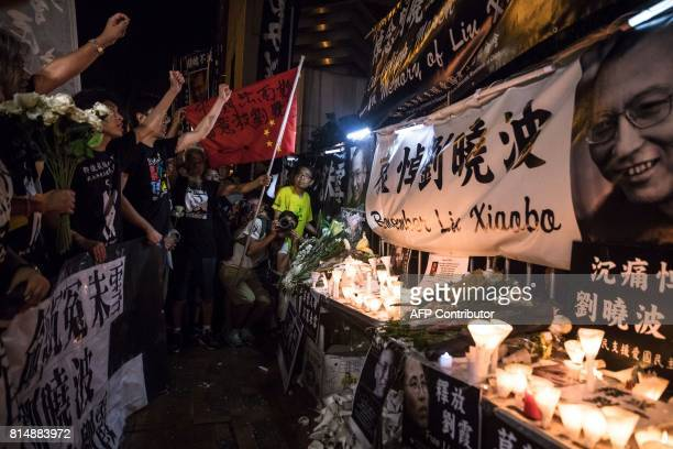 Prodemocracy activists chant slogans in front of a makeshift memorial for the late Chinese Nobel laureate Liu Xiaobo outside the Chinese Liaison...