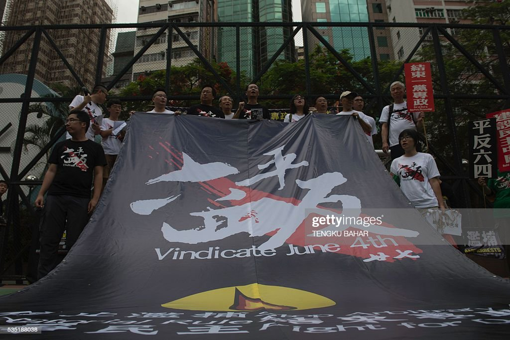 Pro-democracy activists hold a banner during a rally ahead of the anniversary of the June 4, 1989 Tiananmen Square crackdown, in Hong Kong on May 29, 2016. People will gather in Hong Kong on June 4 for the annual remembrance ceremony to mark the 27th anniversary of the Tiananmen Square crackdown. / AFP / TENGKU