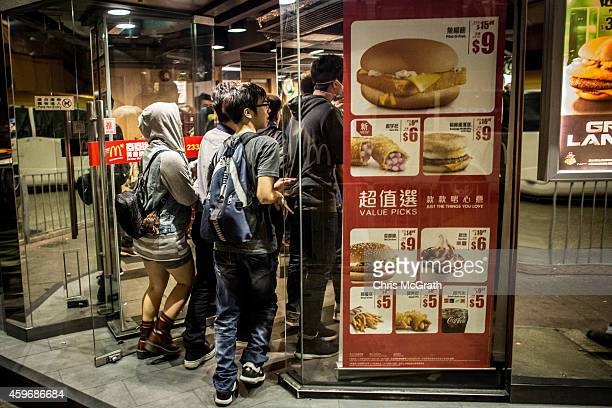 Prodemocracy activists run away from police into a McDonalds store on a street in Mong Kok on November 29 2014 in Hong Kong Clashes between police...