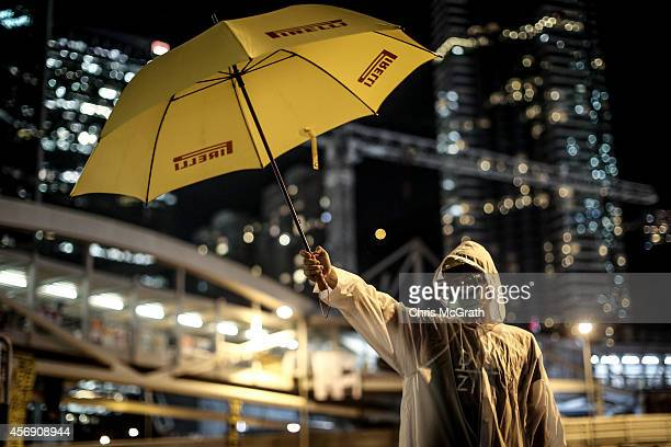 A prodemocracy activists stands with a yellow umbrella as part of an art installation outside Hong Kong's Government complex on October 9 2014 in...