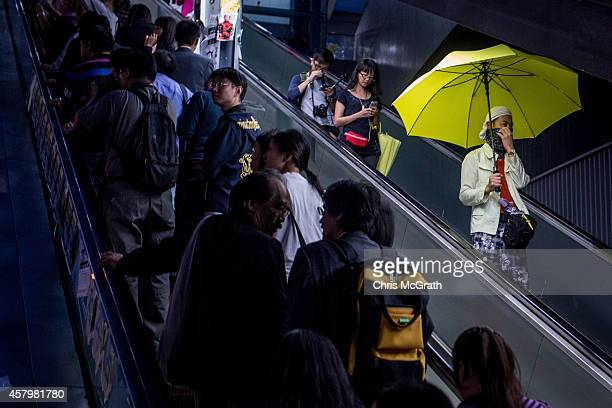 A prodemocracy activists uses an escalator as he holds a yellow umbrella on a street outside Hong Kong's Government Complexon October 28 2014 in Hong...