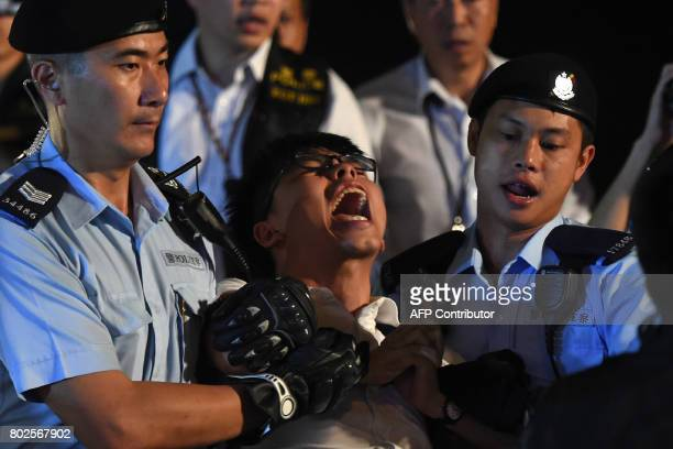 TOPSHOT Prodemocracy campaigner Joshua Wong yells as he is taken away by police after he and other demonstrators staged a sitin protest at the Golden...