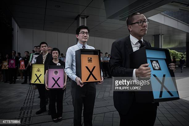 Prodemocracy campaigners display placards symbolising a vote against the government's controversial electoral roadmap outside the city's legislature...