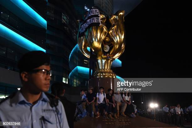 Prodemocracy campaigners including Joshua Wong wait for police to remove them from the base of the Golden Bauhinia statue given to Hong Kong by China...