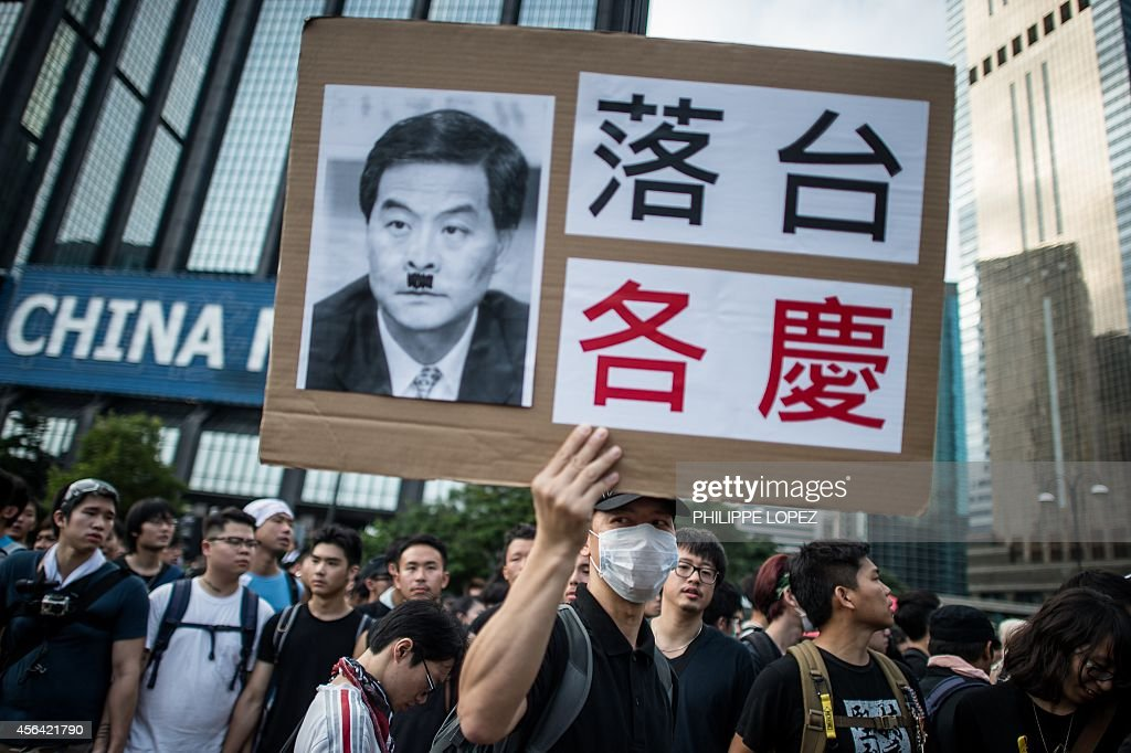 A prodemocracy demonstrator holds a placard depicting Hong Kong chief executive Leung Chunying as Hitler as they gather near a ceremony marking...