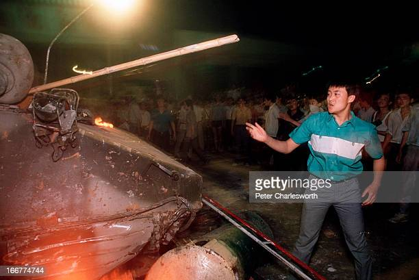 A prodemocracy demonstrator throws a wood pole at a burning armoured personnel carrier during the fighting that raged on Changan Avenue as soldiers...