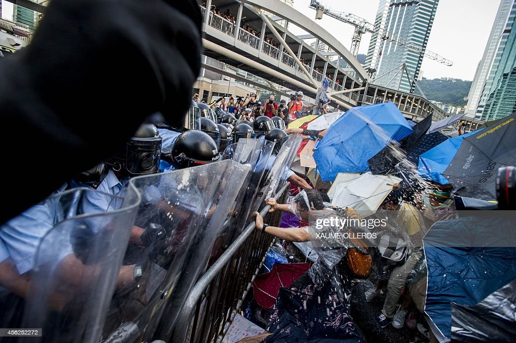Prodemocracy demonstrators are sprayed with pepper spray during clashes with police officers in riot gear during a rally near the Hong Kong...