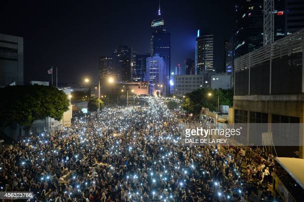 Prodemocracy demonstrators hold up their mobile phones during a protest near the Hong Kong government headquarters on September 29 2014 The ranks of...