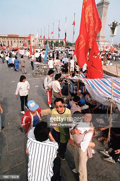 Prodemocracy demonstrators mill about a Tiananmen Square filled with protest flags and temporary encampments Prodemocracy demonstrators filled the...