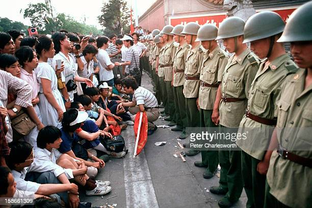 Prodemocracy demonstrators sit in front of soldiers who are lined up standing guard outside the Chinese Communist Party's headquarters on Chiangan...