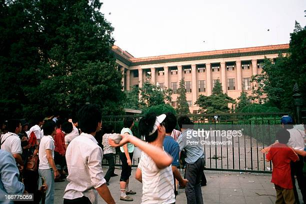 Prodemocracy demonstrators throw rocks and stones at a communist government building near Tiananmen Square a day before the final bloody nighttime...
