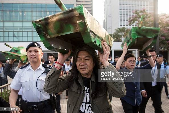 Prodemocracy lawmaker Leung Kwokhung known as Long Hair holds a model tank made of cardboard over his head during a protest against the public...