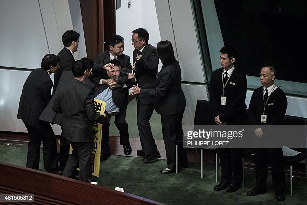 Prodemocracy lawmaker Raymond Chan is taken away after he interrupted the policy address of Hong Kong Chief Executive Leung Chunying by staging a...