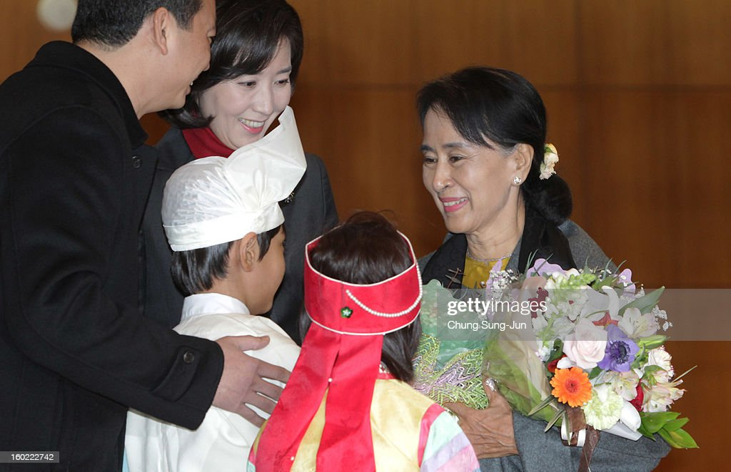 Pro-democracy leader Aung San Suu Kyi (R) recieves flowers from children of National League for Democracy at Incheon International Airport on January 28, 2013 in Incheon, South Korea. Myanmar opposition party leader and Nobel Peace Prize laureate arrived in South Korea for a 5-day visit