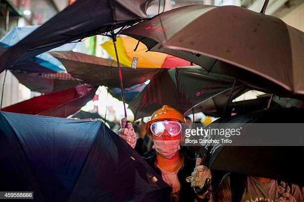 Prodemocracy Occupy Central protester hold on under umbrellas as Police try to clear the streets after agents authorized by bailiff's removed...
