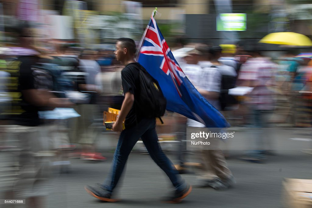 Pro-Democracy protester carries the Hong Kong colonial flag in Hong Kong, July 1 2016. Pro Democracy protesters march as the city marks the 19th anniversary of the handover from Uk to China.