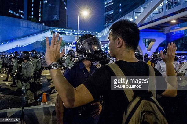A prodemocracy protester faces a policeman in Hong Kong during a demonstration on September 28 2014 Police fired tear gas as tens of thousands of...