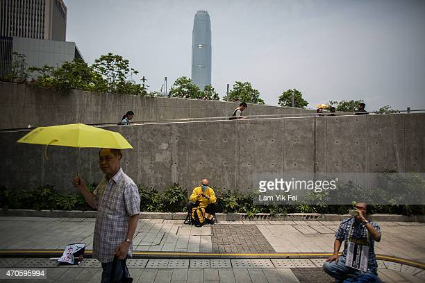 A prodemocracy protester holds a yellow umbrella a symbol of the prodemocracy protests during a demonstration outside Legislative Council in Hong...