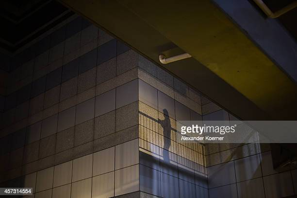 A prodemocracy protester is siloutted while using a mobile device at Admiralty Center on October 17 2014 in Hong Kong Hong Kong Police have begun to...