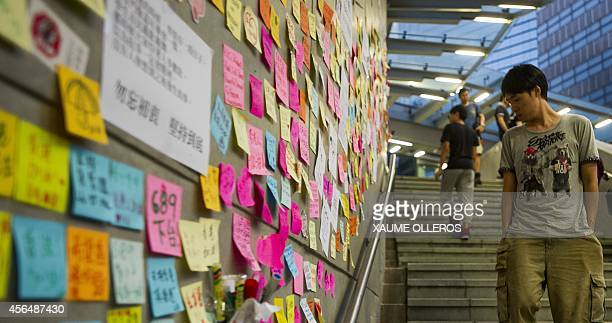 A prodemocracy protester looks at messages stuck on the wall of the Legislative Counsel building in the Admiralty district of Hong Kong on October 2...