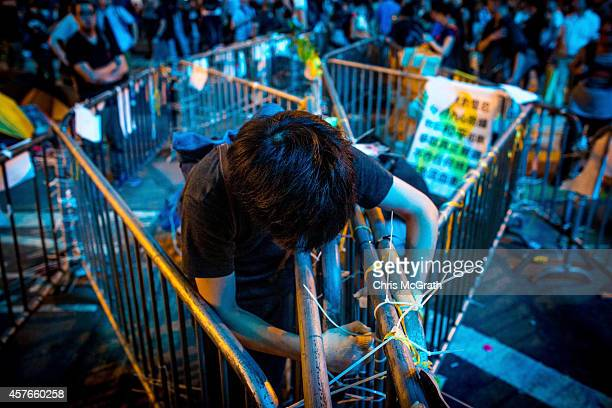 A prodemocracy protester secures a barricade with zip ties in Mong Kok on October 22 2014 in Hong Kong Police have begun to take measures to remove...