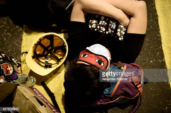 A prodemocracy protester sleeps inside a barricade at Mong Kok on October 20 2014 in Hong Kong Hong Kong Expected clashes between prodemocracy...