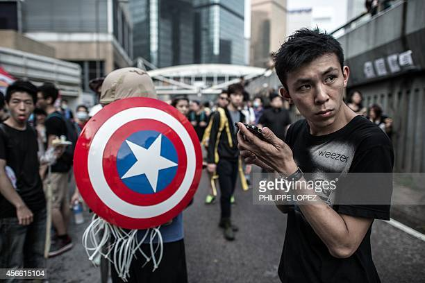 A prodemocracy protester standing next to another one carrying a shield from the 'Captain America' comic book series listens to his phone as they...
