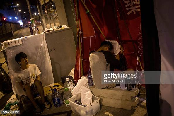 A prodemocracy protester uses a makeshift shower to wash his hair in the early hours of Monday morning outside the Hong Kong Government complex on...