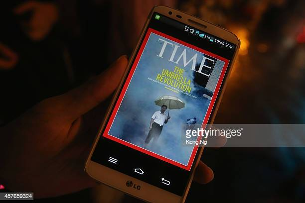 Prodemocracy protester watches a cover photo of Time magazine about Hong Kong protest event on his cellphone on a street in Mongkok district on...