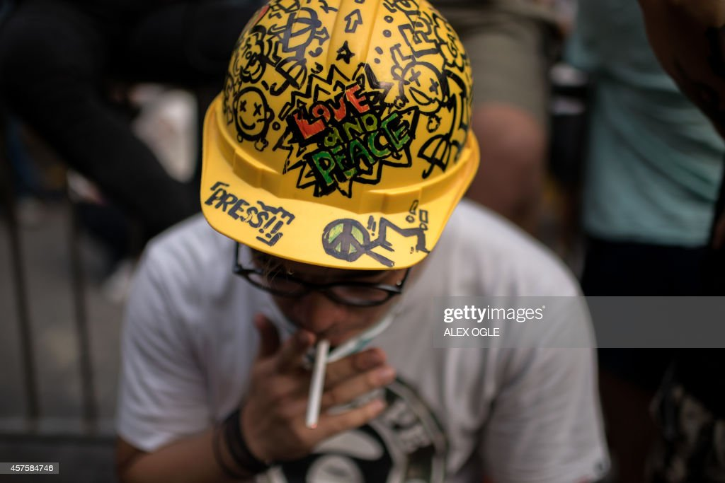 A pro-democracy protester wearing a helmet smokes as he sits next to a barricade opposite the central government offices in the Admiralty district of Hong Kong, after a court injunction ordered the fences to be taken away, on October 21, 2014. Hong Kong authorities and pro-democracy protest leaders sat down on October 21 for talks aimed at ending weeks of rallies that have paralysed the city's streets, on the same day the city's leader ruled out democratic reforms. AFP PHOTO / ALEX OGLE