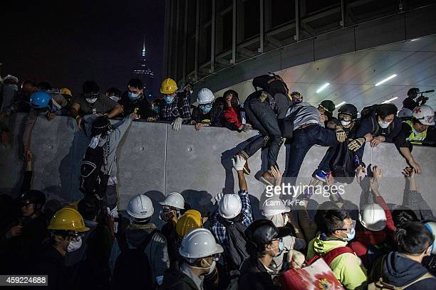 Prodemocracy protesters climb up a wall as police officers disperse them outside the Legislative Council building after clashes with prodemocracy...
