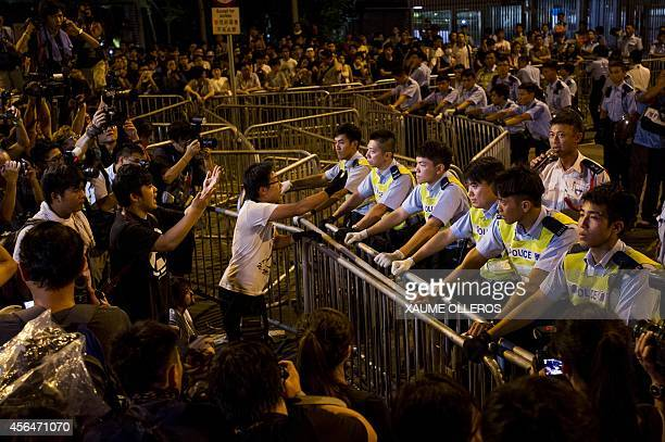 Prodemocracy protesters face policemen as they wait for Hong Kong chief executive outside the Legislative Counsel Office on October 2 2014 in Hong...